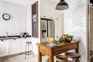 Una cocina con subway tiles y carpintería de hierro