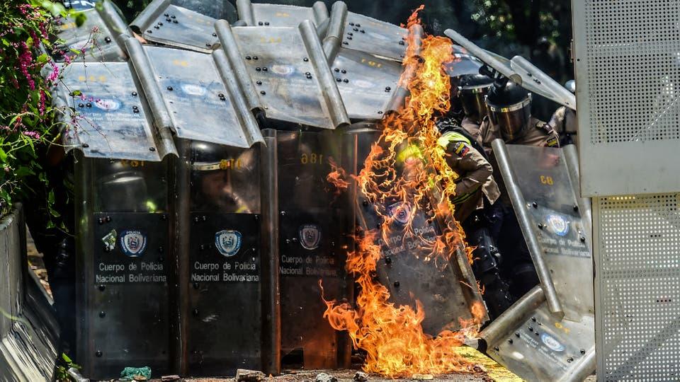 Una bomba molotov explota contra los escudos de la Guardia Nacional. Foto: AFP / Ronaldo Schemidt