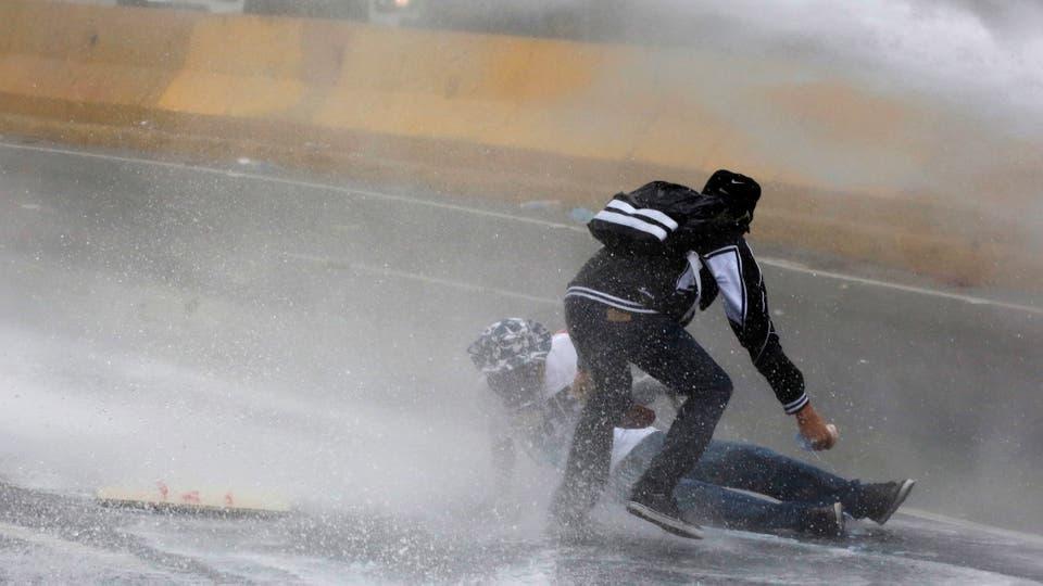 Camiones hidrantes lanzan agua sobre los manifestantes opositores. Foto: Reuters / Marco Bello