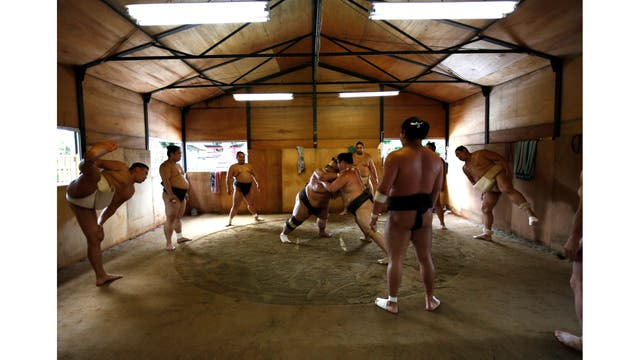 El mongol Tomozuna Oyakata, o maestro del establo Tomozuna (derecha), asiste a la sesión de entrenamiento de sus luchadores en el templo Ganjoji Yakushido en Nagoya