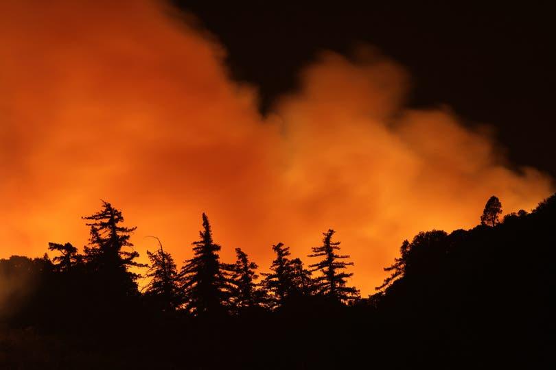 El fuego y el humo se elevan detrás de las montañas. Foto: AFP