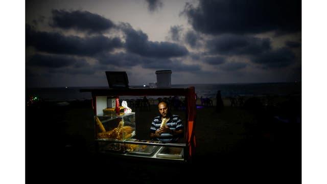Un vendedor ambulante en la playa usa baterías para iluminar