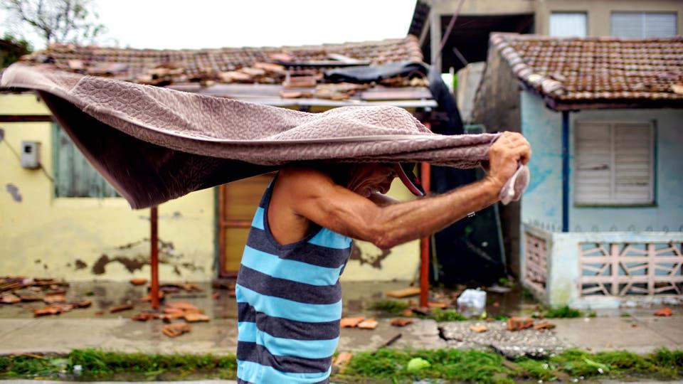 Un hombre se protege de la lluvia. El Huracán Irma se encuentra a 185 km de Florida, EE. UU.. Foto: Reuters / Alexandre Meneghini