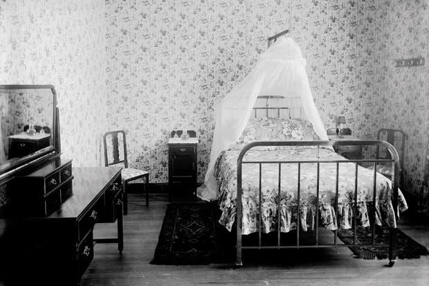 Antes: Pisos de madera, paredes empapeladas y una cama pequeña con estructura de hierro y baldaquino..