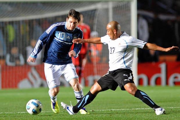 Lionel Messi escapa la marca de Arévalo Ríos.  Foto:AP
