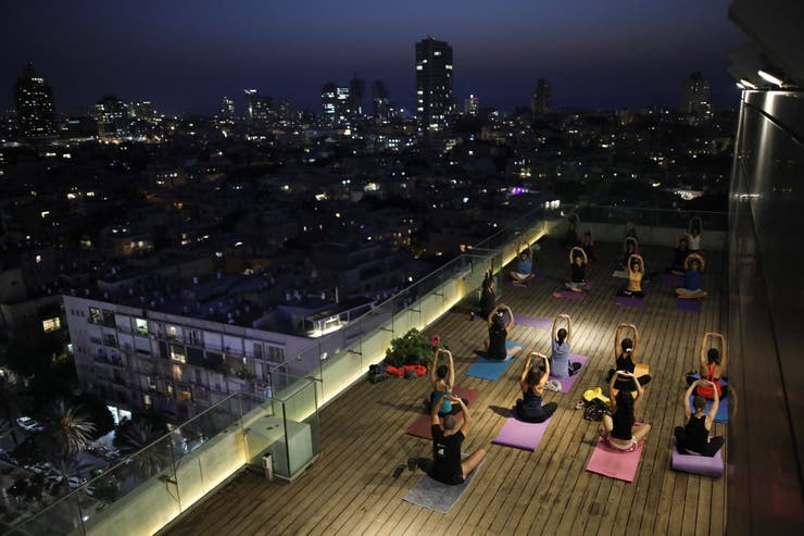 La gente participa en una clase de yoga en la azotea del edificio del municipio de Tel Aviv