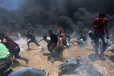 Manifestantes palestinos huyen del fuego israelí y del gas lacrimógeno durante la protesta