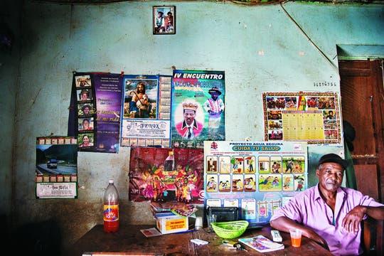 Todo humildad. El rey trabaja en la pequeña tienda construida en la planta baja de su hogar. Sobre la pared, un afiche recuerda su coronación.