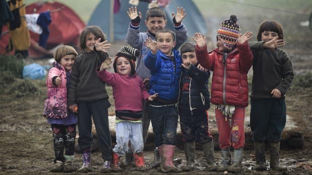 Chicos sirios y afganos saludan a la prensa en un campo de refugiados en Grecia