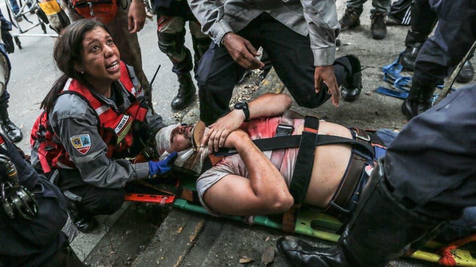 Servicio de urgencias traslada a un herido a causa de los enfrentamientos con la policia. Foto: AP / Fernando Llano