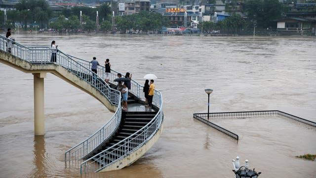Un grupo de personas observa la inundación del río Li en Guillin