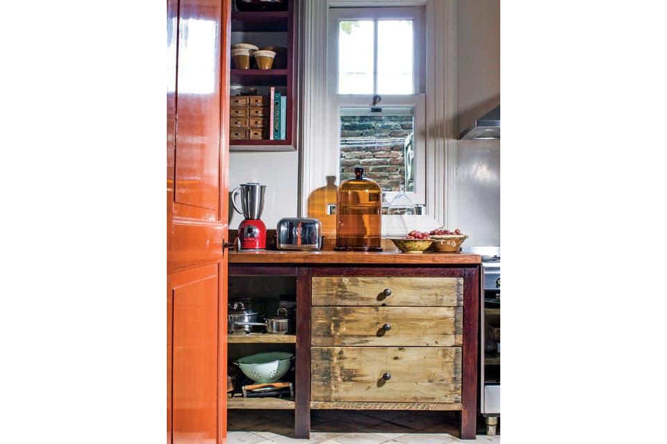 Con patas lustradas y contrastes de tonos y texturas, el mueble de cocina es a la vez cajonera, estantería y mesada de madera (Pablo Ledesma)..  Foto:Living /Santiago Ciuffo