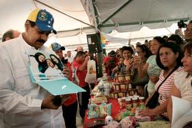 Maduro visitó ayer el Mercal, en Caracas, y aprovechó para mostrar las fotos de Chávez y sus hijas