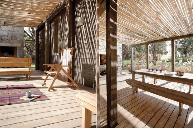 Un rincón del deck del frente donde se ve el revestimiento en pino pintado de negro y la zona de bancos y reposeras que miran al jardín..