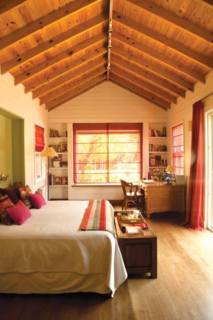 El dormitorio principal tiene salida directa al jardín. Las cortinas reiteran el color de las celosías pintadas de rojo 'Orquídea Rubí' de Alba..  Foto:Living /Javier Csecs
