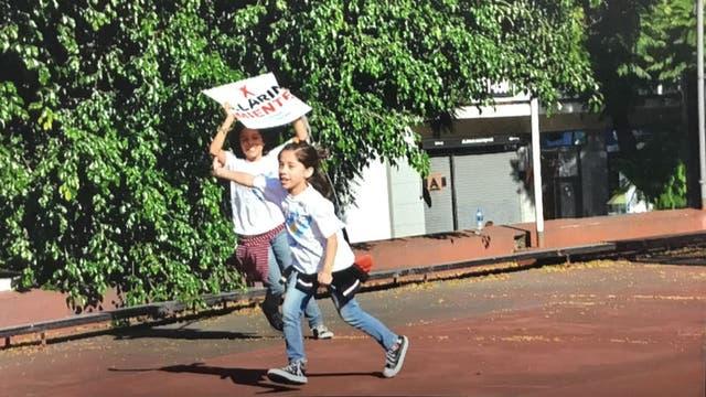La foto de dos niñas vestidas con remeras de La Cámpora y un cartel contra Clarín