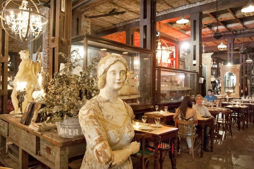Estatuas y arañas antiguas se mezclan entre las mesas del restaurante Nápoles