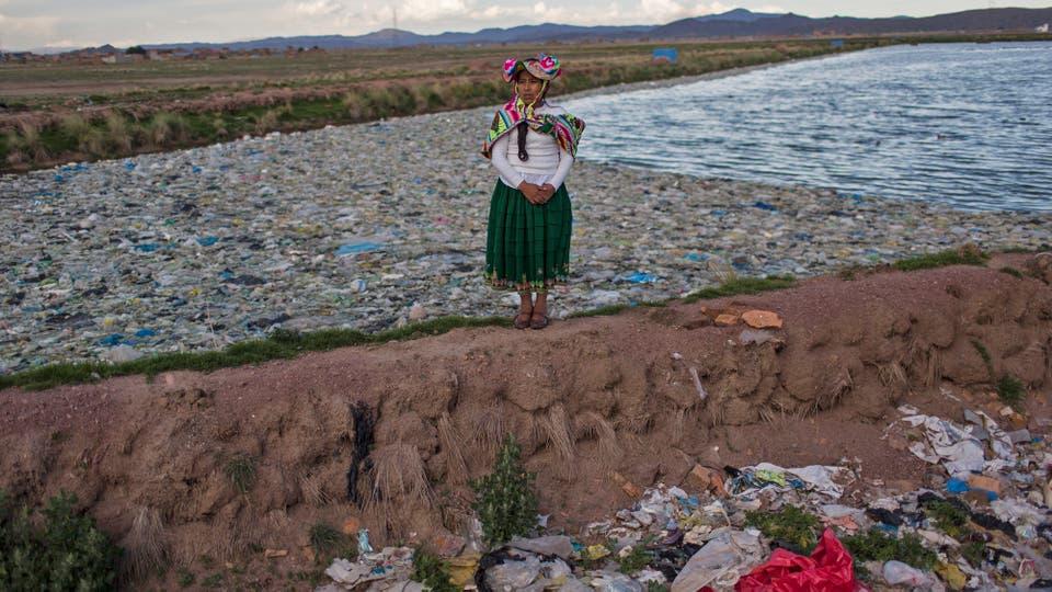 La activista ambientalista Maruja Inquilla posa para una foto junto a una planta municipal de tratamiento de residuos con agua que desemboca en el Lago Titicaca, en Juliaca, en la región de Puno, Perú