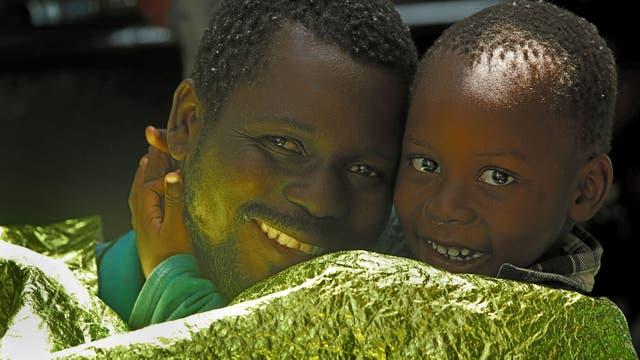 Un emigrante y su hijo descansan en la nave de Malta, la ONG Migrant Offshore Aid Station (MOAS), después de ser rescatados en el centro del Mediterráneo frente a la costa libia, mientras el barco se dirige hacia Italia
