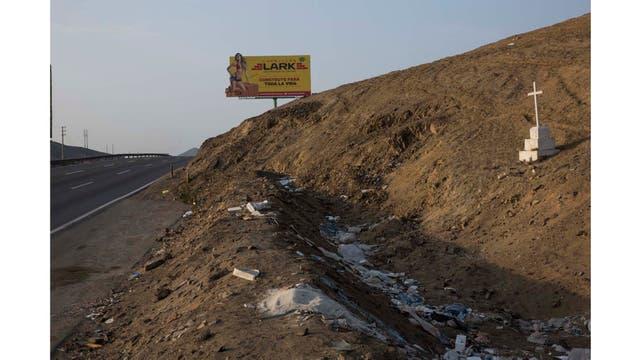 Un cartel publicitario de materiales de construcción se encuentra a lo largo de la Carretera Panamericana, donde una cruz marca el lugar donde alguien fue asesinado, en el lado sur de Lima