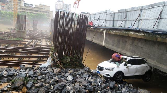 Un auto que fue arrastrado por la corriente quedó atascado contra un puente en Quanzhou, provincia de Guangx