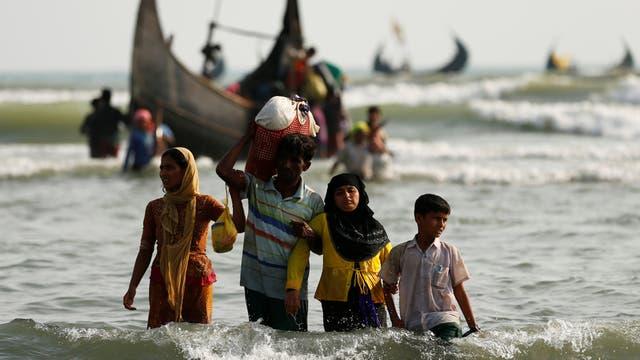 Refugiados Rohingya caminan a la orilla con sus pertenencias después de cruzar la frontera de Bangladesh-Myanmar en barco a través de la bahía de Bengala