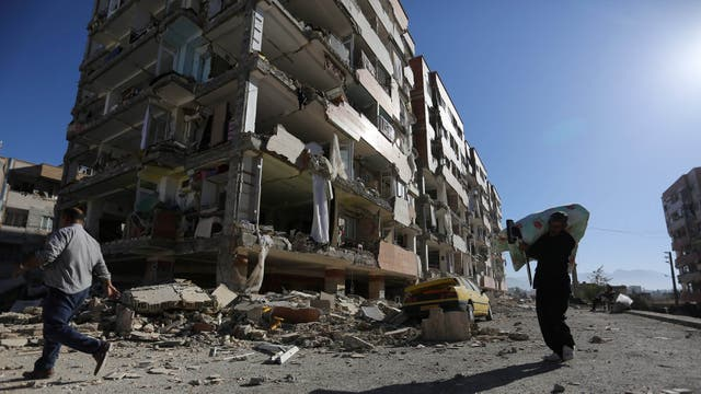 Varias personas caminan por las calles de la ciudad derrumbada