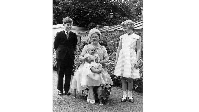 Esta foto de archivo tomada el 4 de agosto de 1960 muestra a la Reina Isabel, sosteniendo al Príncipe Andrés en su regazo, rodeada por el príncipe Carlos y la Princesa Ana, mientras celebra su 60 cumpleaños en el jardín de Clarence House en Londres