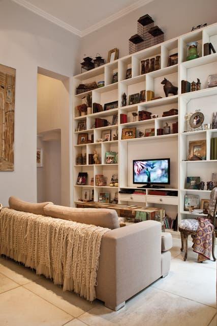El sofá, tapizado en tono neutro, tiene en el respaldo una tela que Inés compró originalmente para hacer vestidos y almohadones con estampas de zapatos (Pulga Chic)..  Foto:Living /Magalí Saberian