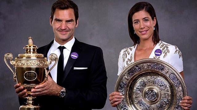 Roger Federer y Garbiñe Muguruza con los trofeos de campeones