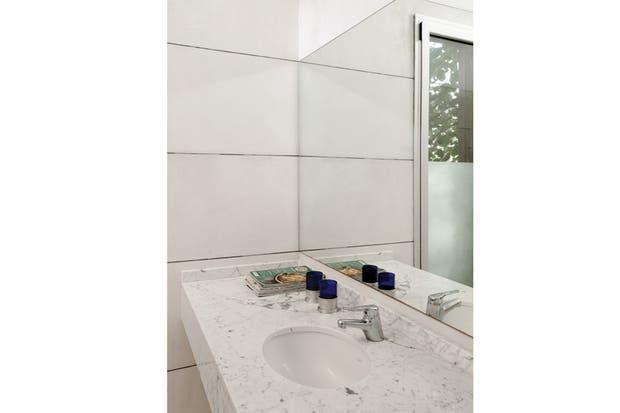 El baño en suite con mesada de mármol y revestimiento de cemento organizado entre juntas de vidrio. Artefactos estándar (Ferrum) y grifería cromada (FV)..