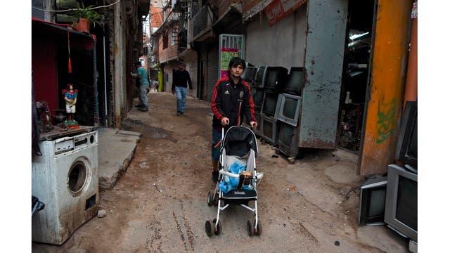 Un hombre empuja un cochecito con un perro a lo largo de una calle de la Villa 31 en Buenos Aires, Argentina