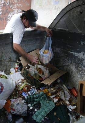 Una persona revuelve la basura en busca de comida, en el barrio de Palermo