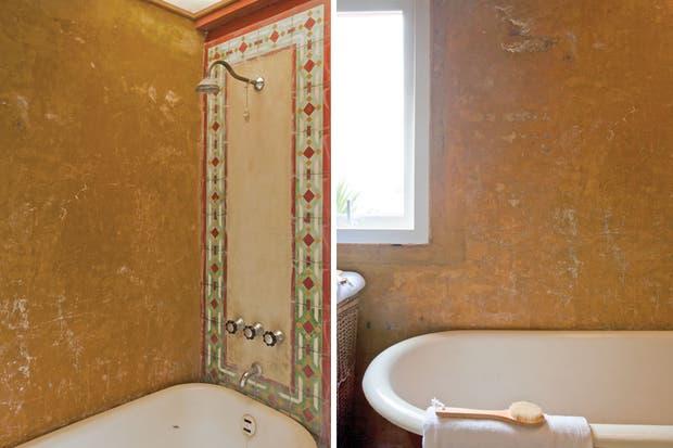 En el baño con paredes de cemento alisado envejecido, antigua bañera. Sobre la bañadera, toalla de algodón y cepillo madera (Falabella).