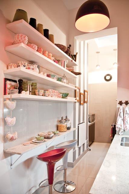Los muebles de la cocina (Reno) van muy bien con los estantes (Imagina Muebles), de donde cuelgan tres gallinitas de tela (María Pancha)..  Foto:Living /Magalí Saberian