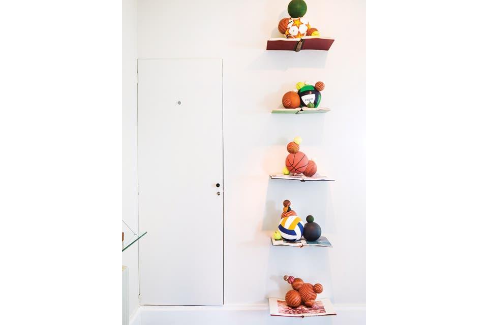 La instalación de Mariana Tellería se ve al entrar en la casa y está junto al placard de recepción: pelotas ensambladas y abolladas sobre libros enciclopédicos.  Foto:Living /Santiago Ciuffo