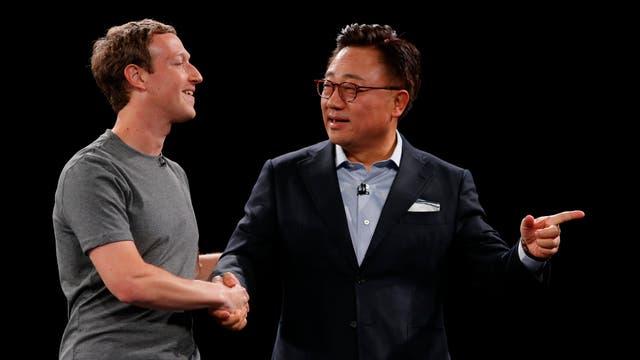 Mark Zuckerberg le da la mano, en el escenario, a DJ Koh, jefe del negocio de smartphones de Samsung