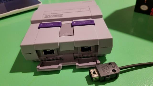 El conector se encuentra oculto en la parte frontal de la consola retro