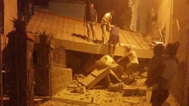 Un grupo de personas remueve escombros