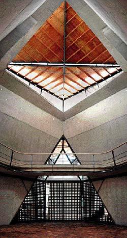 Vista interior de la Capilla, orientada hacia la entrada: arriba, la luz cenital que provee el techo inclinado; abajo, transparencias veladas