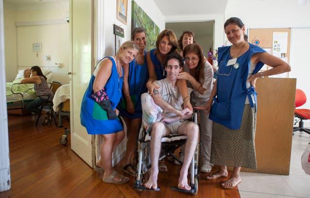 Rodeado de cariño: un huésped del hospice San Camilo, junto a un grupo de voluntarias.