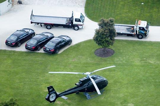 Camiones esperando para llevarse los autos de lujo en la mansión de Dotcom, uno de los dueños de Megaupload. Foto: AP