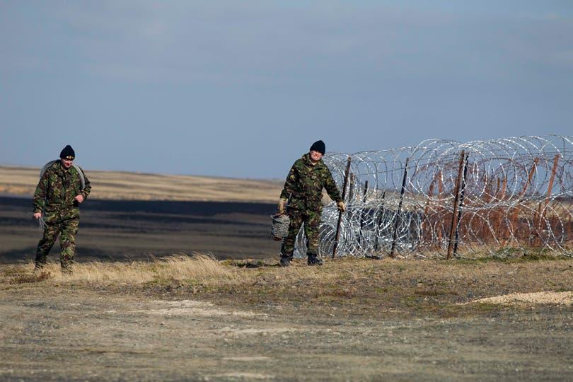 Dos militares ingleses colocan alambres de púas en la base militar Mount Pleasant. Foto: LA NACION / Rodrigo Néspolo