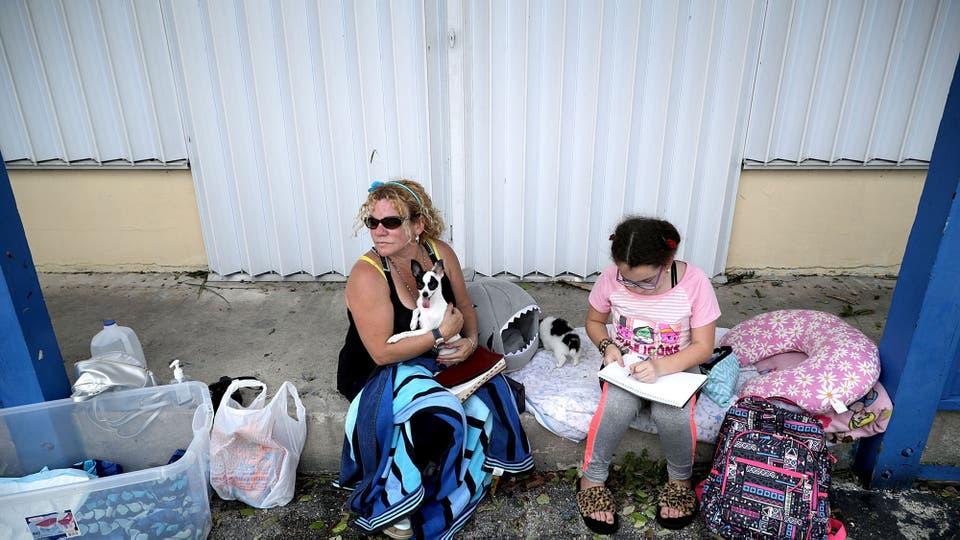 Una familia espera poder regresar a su hogar. Foto: AFP