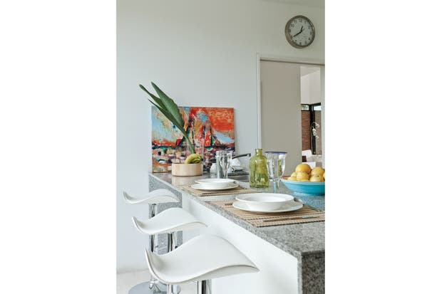 Comunicada con el comedor y el pasillo de entrada, la cocina es un espacio de paso continuo con doble circulación. Tiene muebles laqueados (Bombicino Estudio Cocinas), una mesada de mármol (Mármoles Dodera) y un desayunador con tres banquetas..