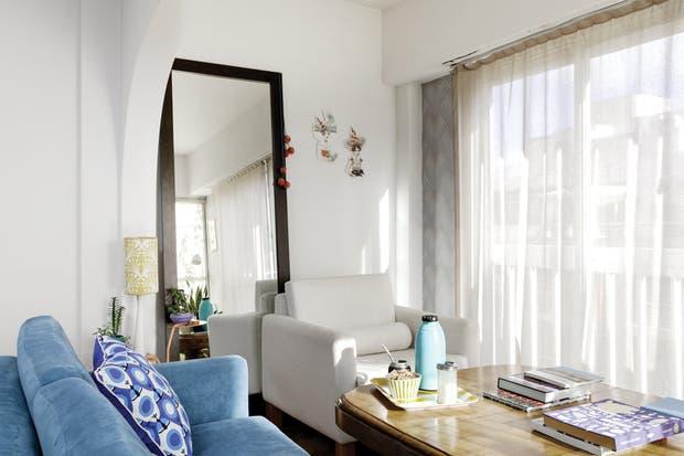 El sillón Hugo en lino afro natural está frente a un gran espejo con marco de madera (La Española)..