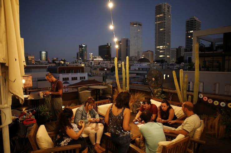La gente socializa en la azotea del Hotel Brown, que sirve como un lugar de bar y evento