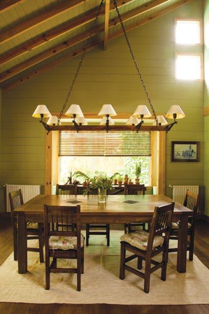 La lámpara que la acompaña es un cricket de Ford T: al moverlo, la pantalla sube y baja; la mesa de comedor estilo campestre. La luminaria colgante de diez pantallas sostenidas por un durmiente; alfombra color hueso (todo de Villatte)..  Foto:Living /Javier Csecs