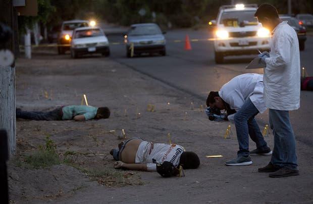 Investigadores sacan fotos de la escena del crimen en Navolato, Sinaloa