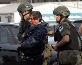 Un trabajador de la línea 60, herido, es retirado de la Panamericana por dos efectivos de Gendarmería